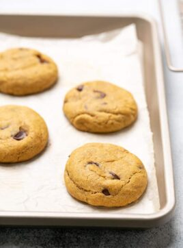 Four baked pumpkin cookies on white paper on baking tray with wire rack on the side