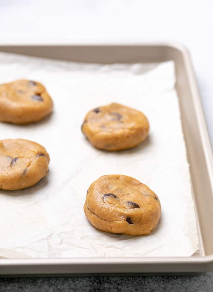Four disks of raw pumpkin cookie dough on white paper on a baking sheet