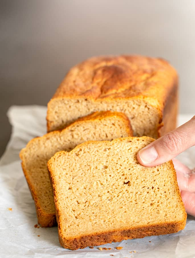 Hand taking a slice of gluten free brown bread