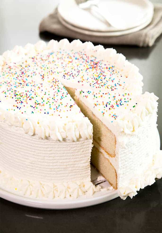 A slice of vanilla cake being taken from a cake with vanilla ermine frosting