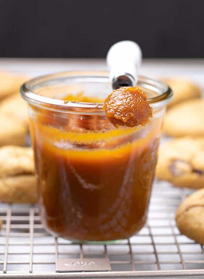 Pumpkin butter in small glass canning jar with some on small cheese knife on wire rack with cookies