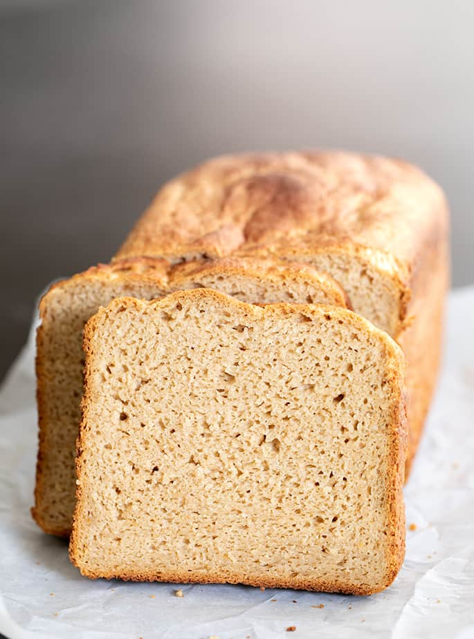 Slice of gluten free brown bread leaning against rest of loaf