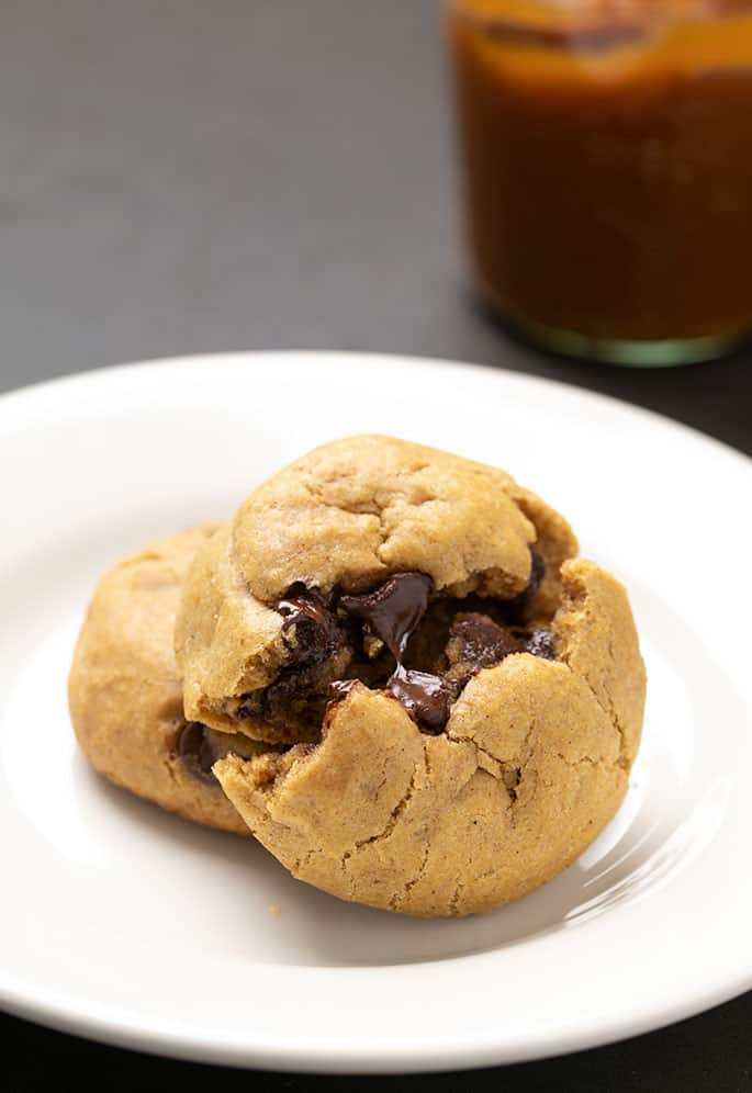 Two pumpkin chocolate chip cookies on small white plate with mason jar of pumpkin butter in background and one cookie broken in half revealing melted chocolate chips