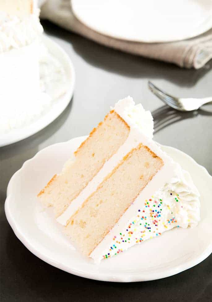 A slice of vanilla layer cake on a plate