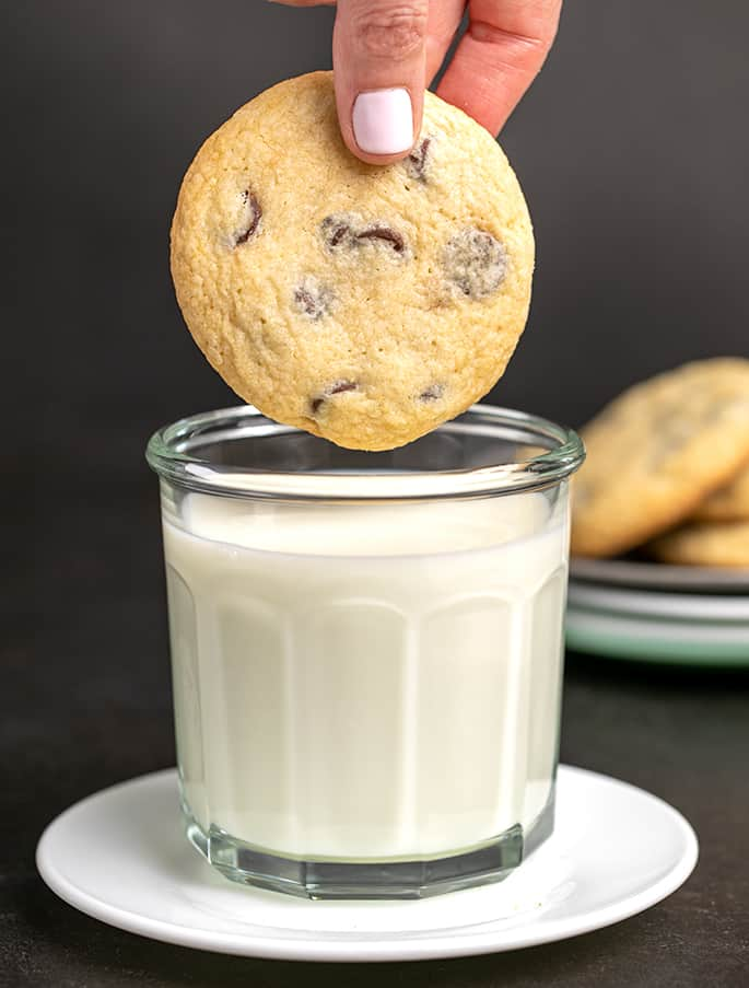 Fingers about to dip a chocolate chip cookie in a large glass of milk on a small white plate