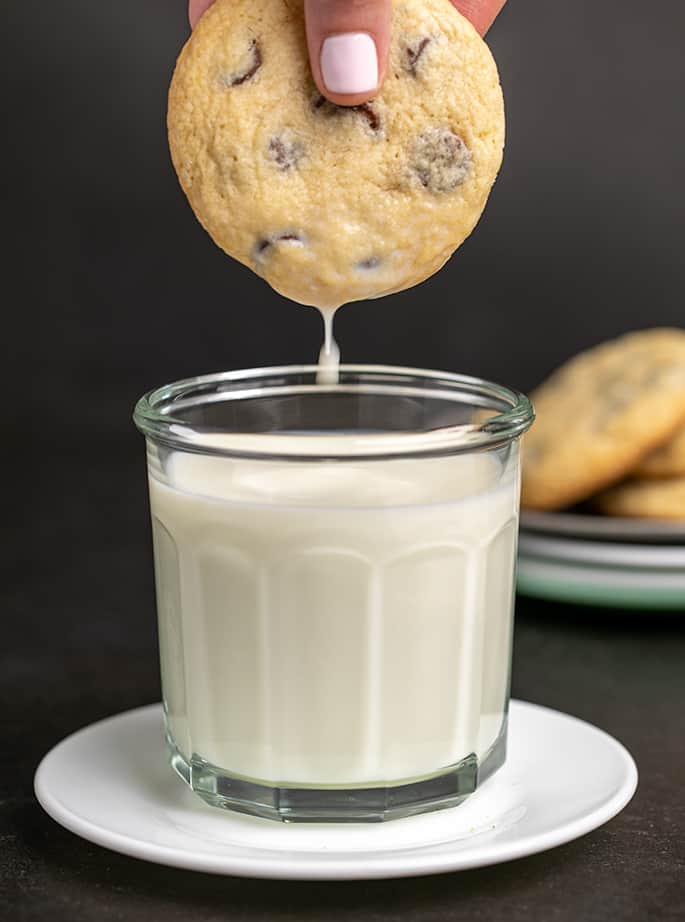 Fingers pulling out chocolate chip cookie from glass of milk on white plate with milk dripping off the cookie