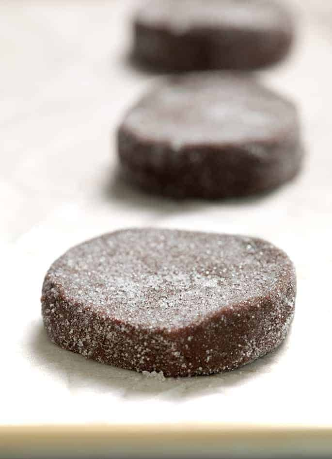 Raw shaped brownie cookie dough with sugar coating on white paper