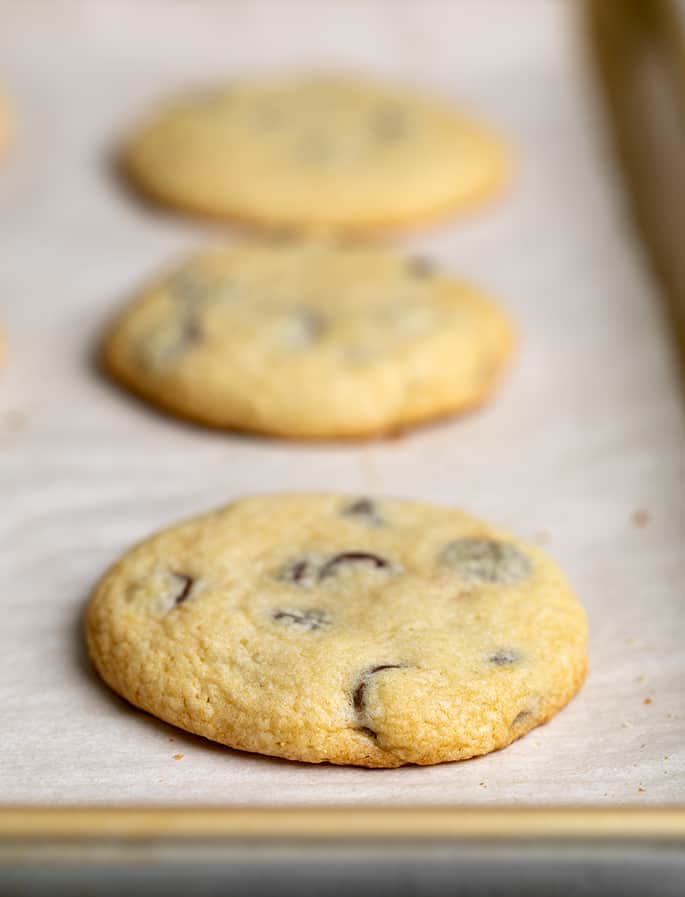 Side angle image of 3 baked soft chocolate chip cookies on white paper on baking tray