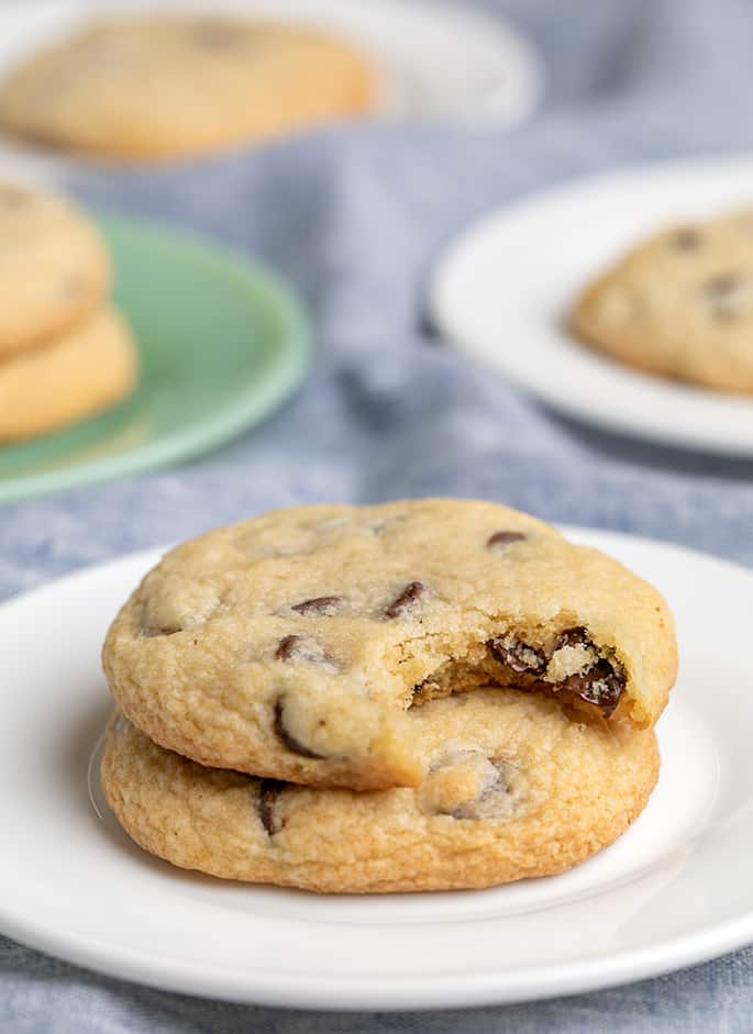 Two chocolate chip cookies on a small white plate one with a bite taken and other cookies on plates in background all on a light blue cloth