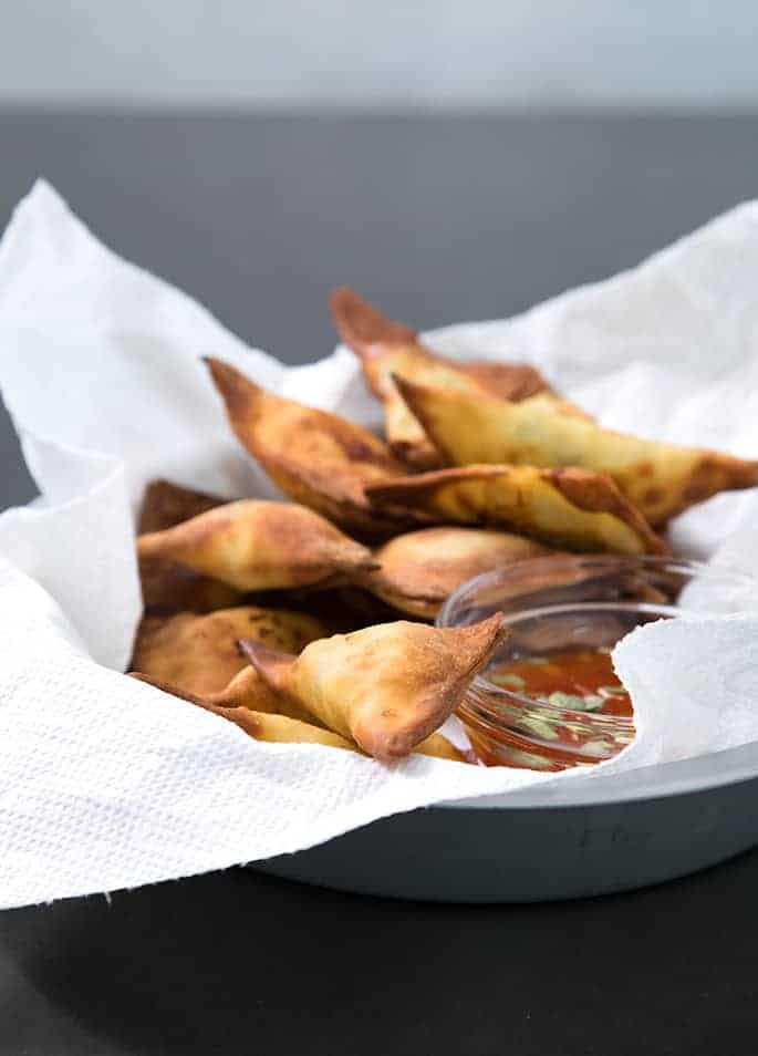 Air fried won tons on white paper towels with dipping sauce