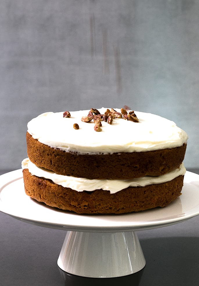 Two layers of carrot cake with frosting in between and on top