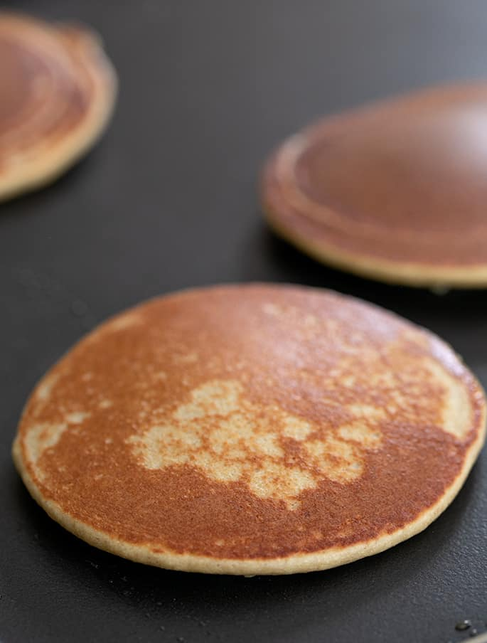 Protein pancake cooking on griddle with cooked side up