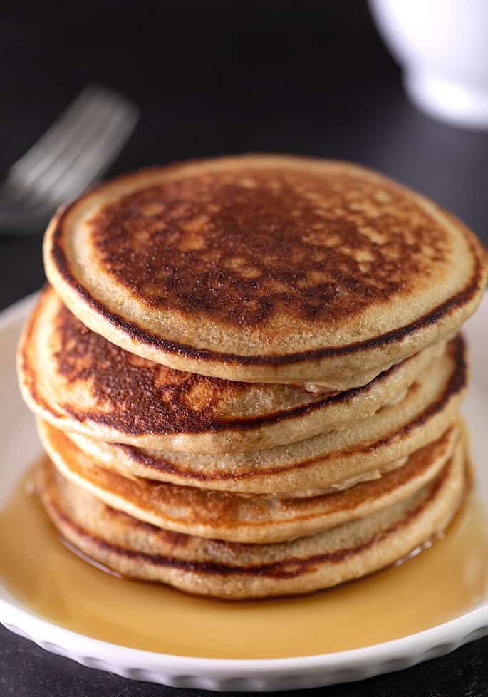 Protein pancakes in a stack on a small plate with syrup