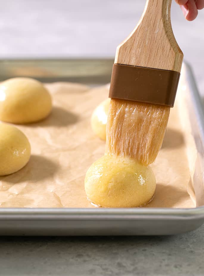 A pastry brush on top of a raw ball of pan de bono