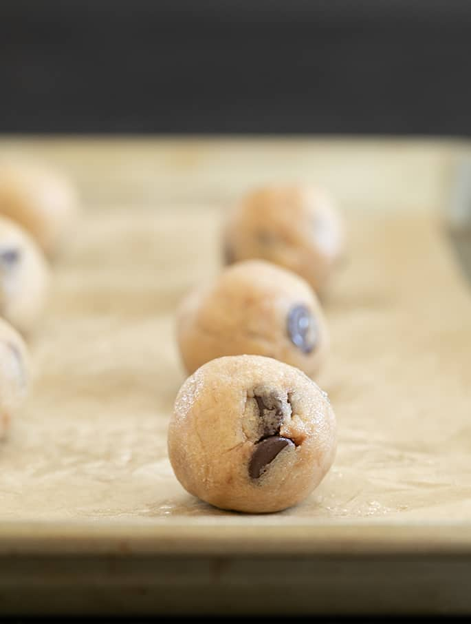 Raw balls of Mrs. Fields Chocolate Chip Cookie dough on tray