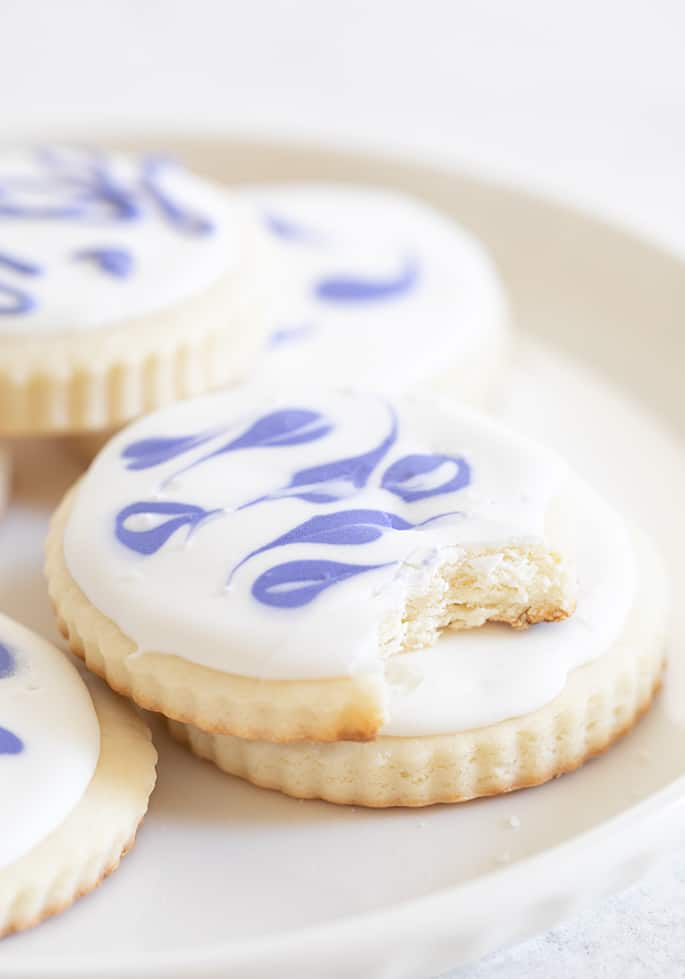 Cream cheese sugar cookies on a plate one with a bite taken