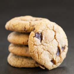 stack of 4 chocolate chip cookies with a fifth on its side leaning against the stack