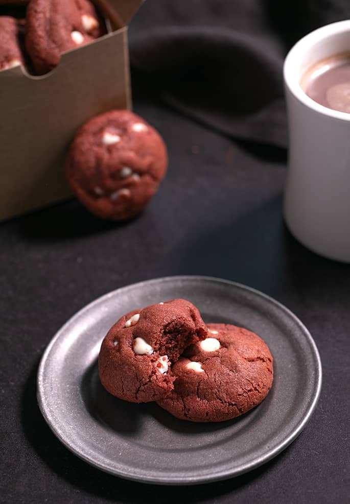 Two red velvet white chocolate chip cookies on a small plate