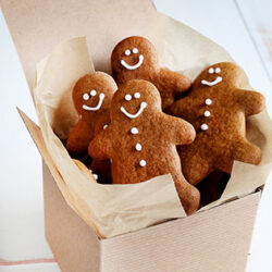 small image of small kraft box of gingerbread men poking out on white surface