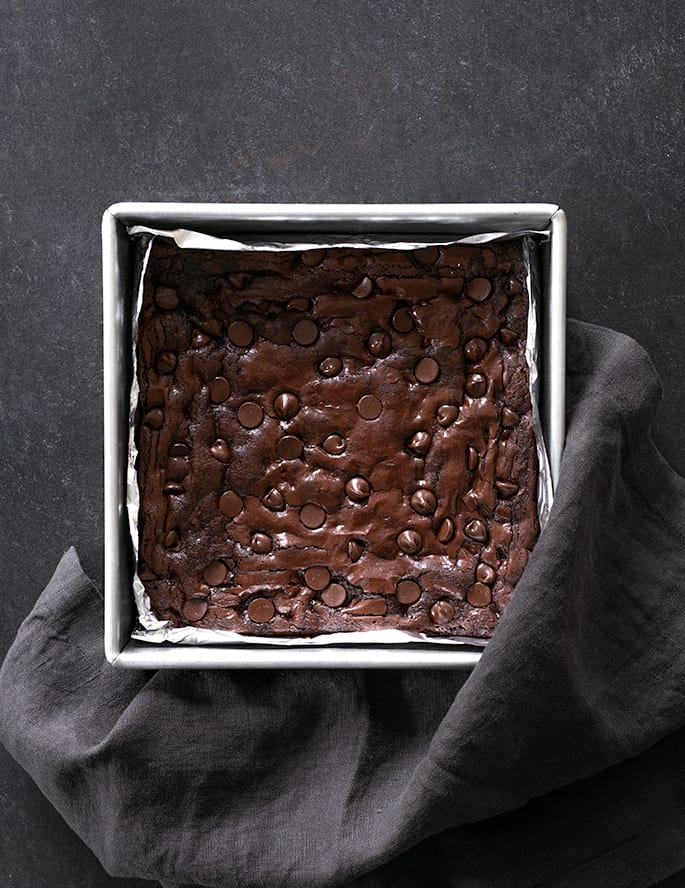 Baked gluten free brownies with chocolate chips on top in metal baking pan lined with foil with a gray cloth touching the pan