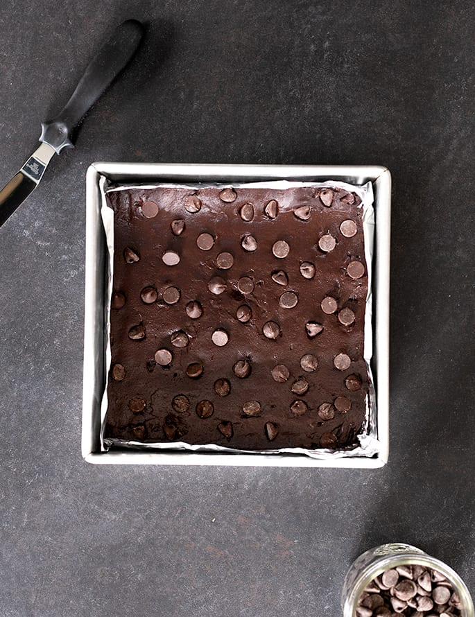 Overhead image of raw brownie batter in lined square metal baking dish with small offset spatula next to the pan