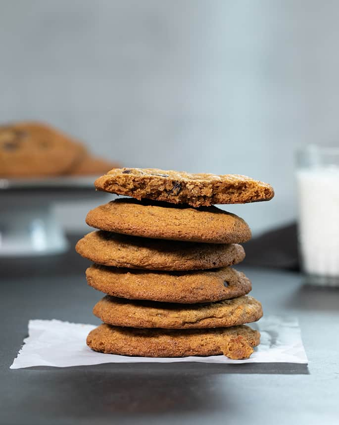 A stack of Paleo chocolate chip cookies with one broken on top