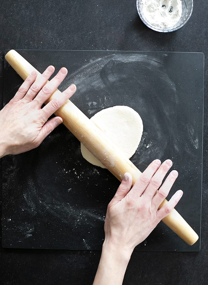 Overhead image of hands rolling out oval dough with a rolling pin