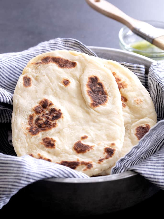 Pieces of cooked gluten free naan bread in striped cloth