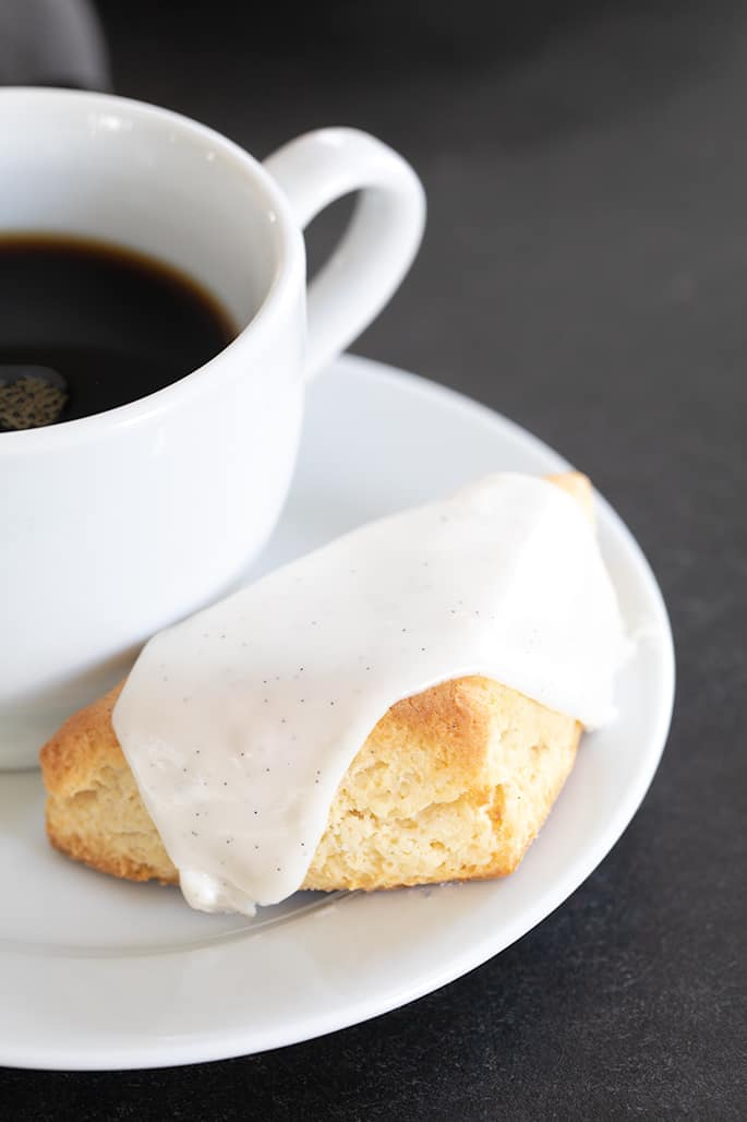 A close up of a vanilla scone with white icing and coffee on a small plate