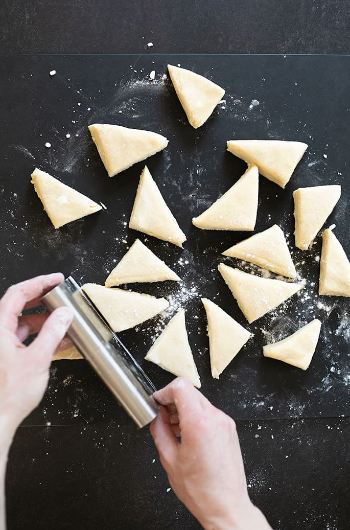 Hands cutting triangles of dough