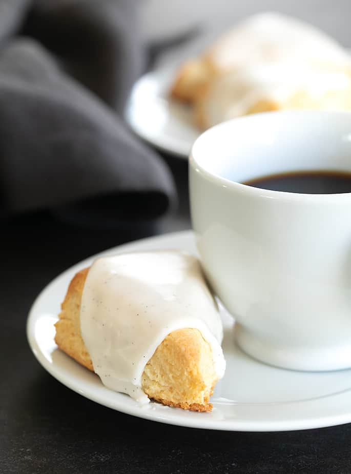 A close up of an iced vanilla scone with a cup of coffee on a plate