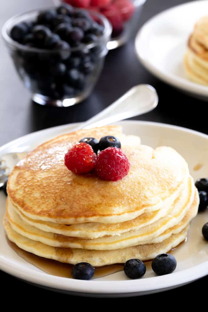 A stack of gluten free pancakes on a plate with a fork and berries