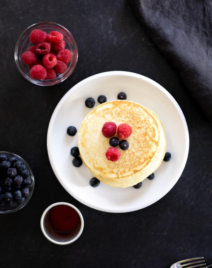 Overhead image of pancakes with berries on a plate