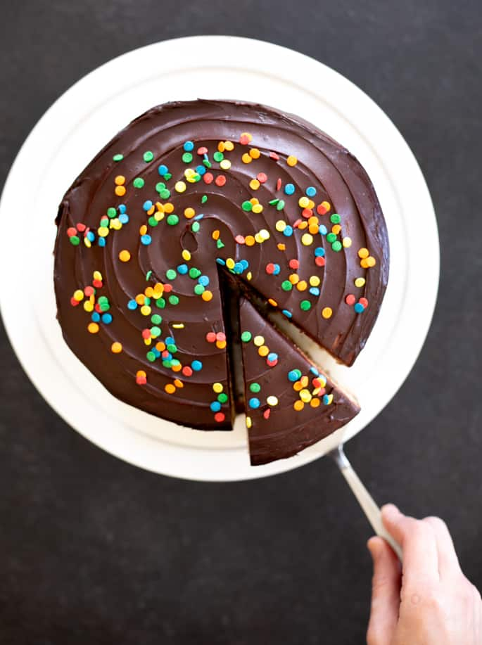 This classic gluten free birthday cake is a funfetti vanilla layer cake filled with chocolate sour cream frosting and topped with chocolate icing. It's your new go-to birthday cake.