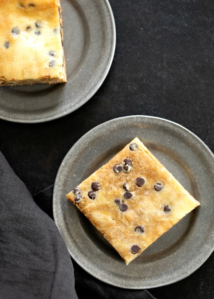Overhead image of two chocolate chip cheesecake blondies on small plates