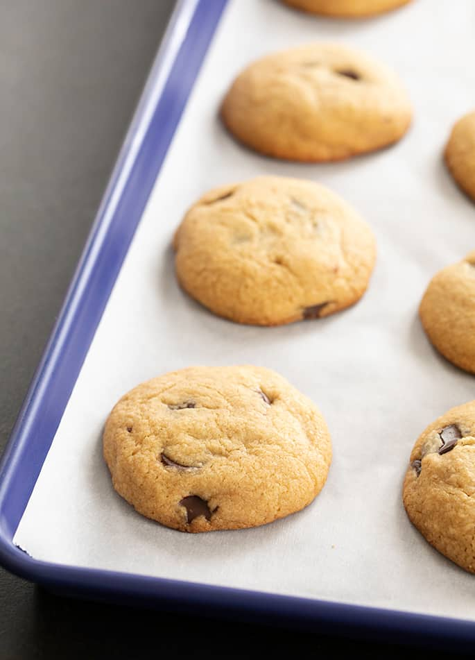 Peanut butter chocolate chip cookies on white paper on a blue tray