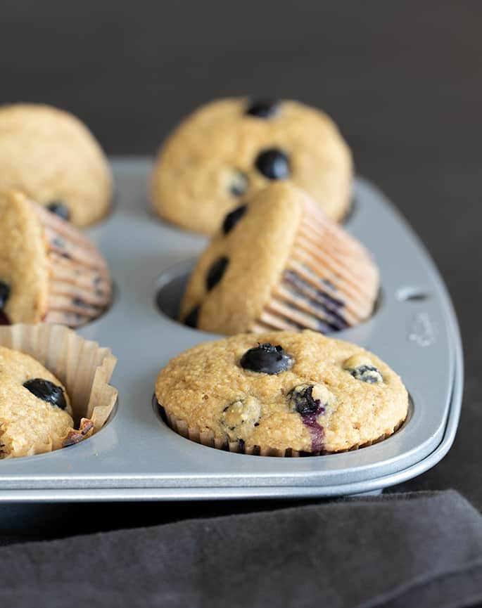 Image of a muffin tin with healthy blueberry muffins.