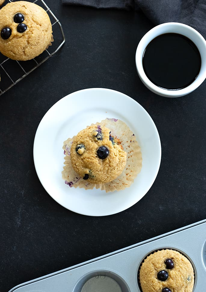 A plate with a cup of coffee, with a blueberry muffin overhead