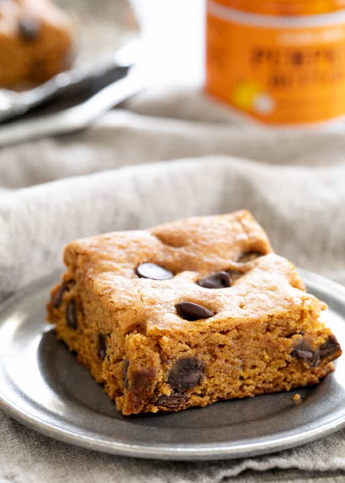 A gluten free pumpkin chocolate chip square on a pewter plate