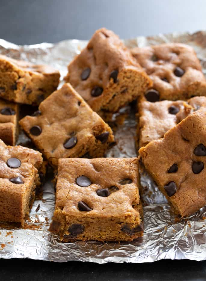 Squares of gluten free pumpkin chocolate chip in a pile on foil.