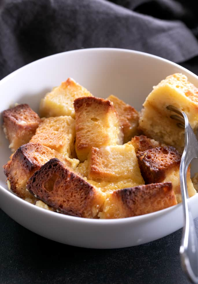A bowl with a forkful of gluten free bread pudding.