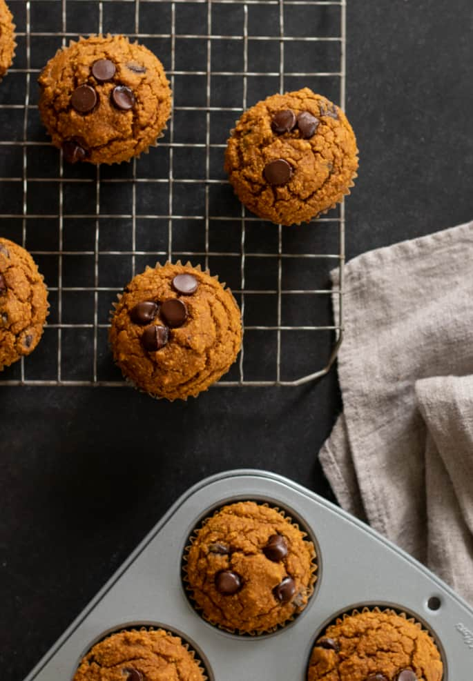 Overhead image of Healthy pumpkin breakfast muffins in muffin tin and cooling on wire rack.