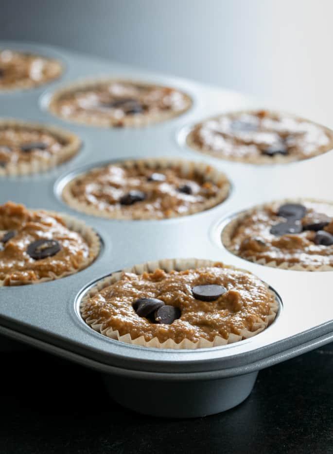 Healthy pumpkin breakfast muffin batter raw in muffin tin.