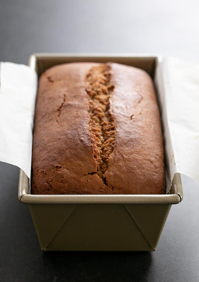 Whole, unsliced gluten free gingerbread loaf still in the baking pan.