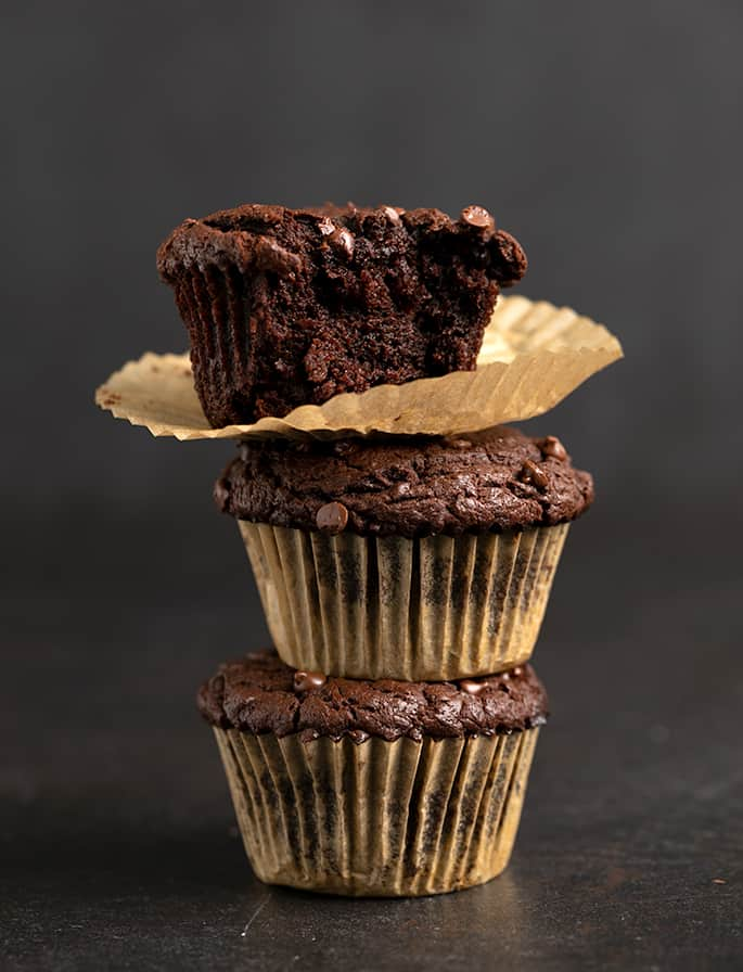 Stack of 3 brown muffins in light brown liners with one liner peeled down and a bite taken on a black surface