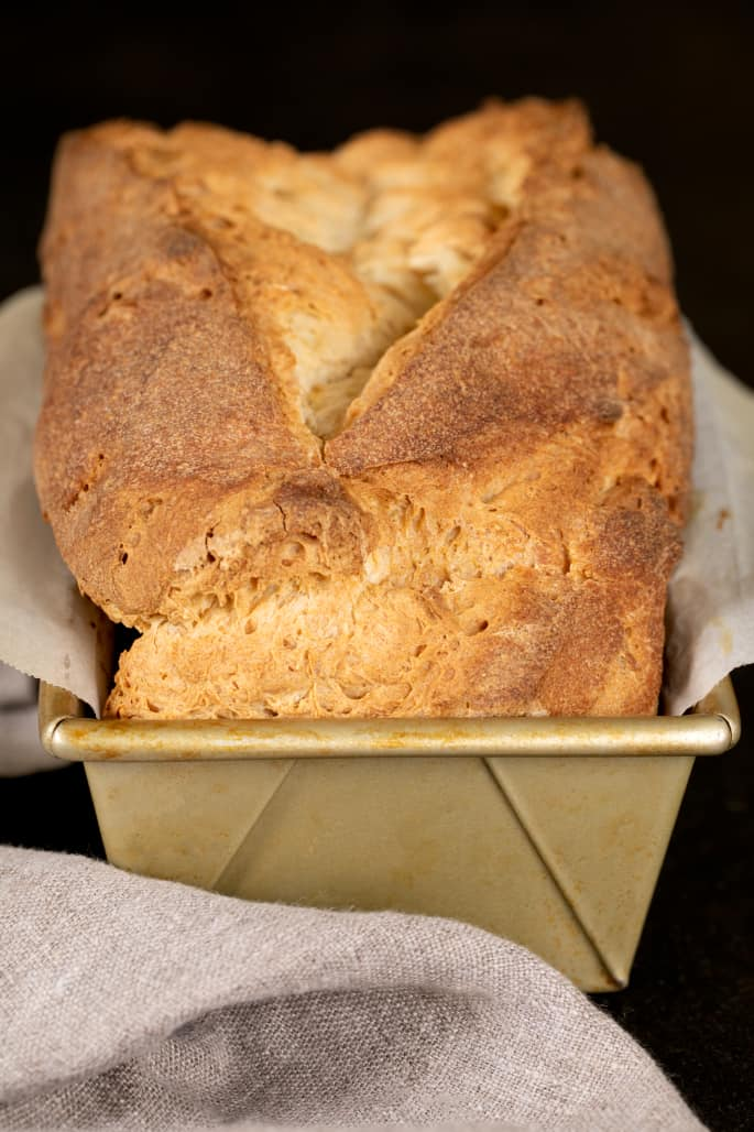 Tom's gluten free sandwich bread loaf shown in the loaf pan, just baked and mostly cool.
