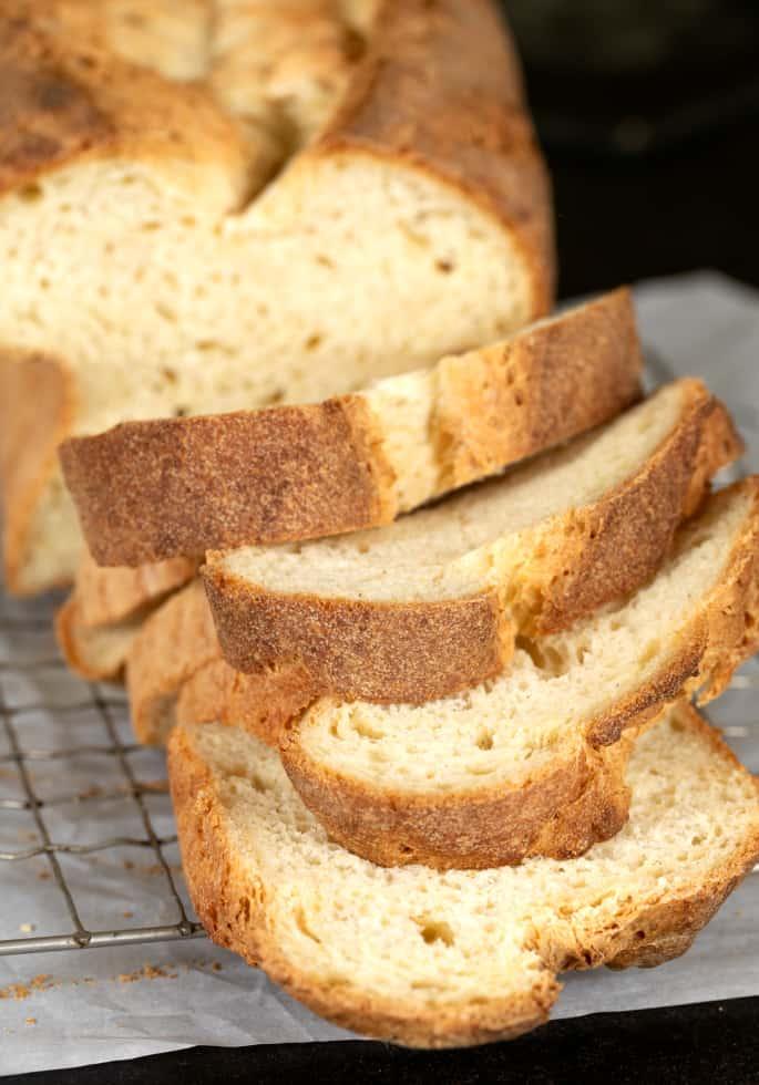 Tom's gluten free sandwich bread shown as it's being sliced.