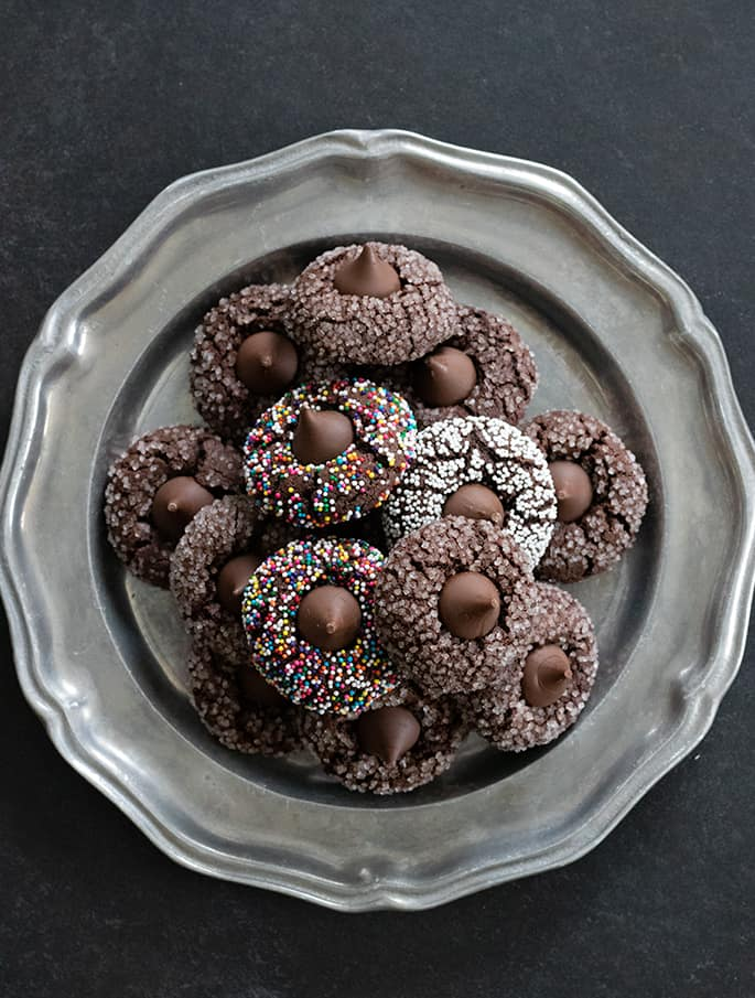 Overhead image of platter of gluten free chocolate kiss cookies, some with nonpareils and others with coarse sugar on the outside.