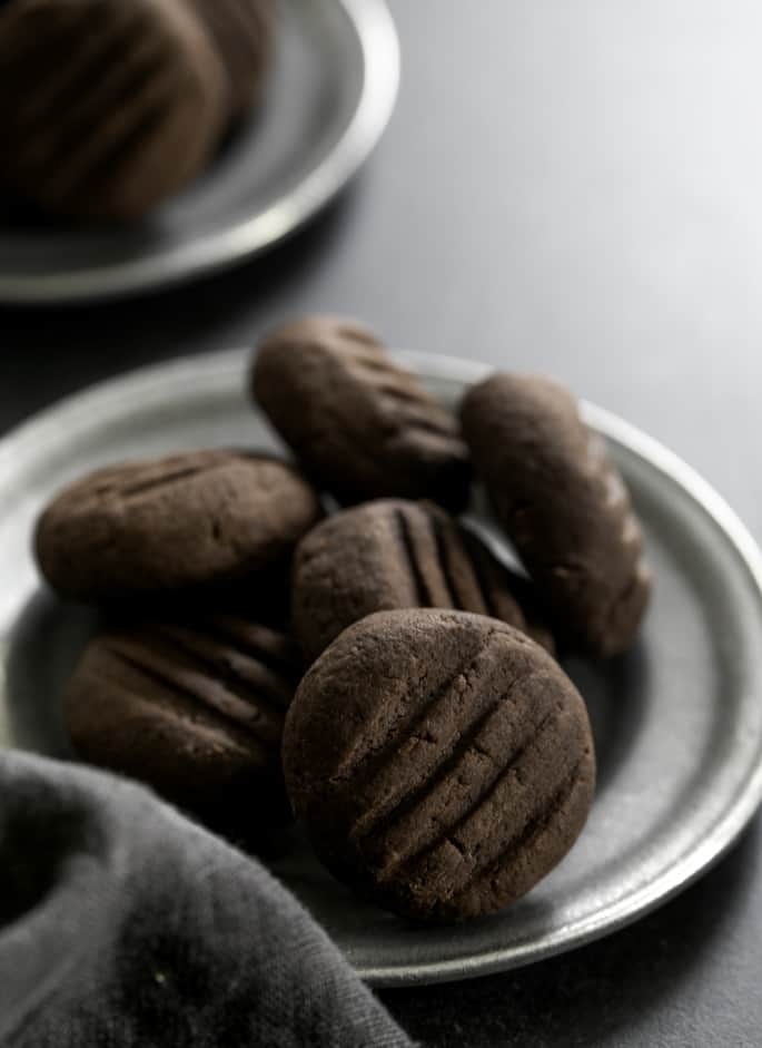 Chocolate gluten free meltaway cookies on a small plate, being served.