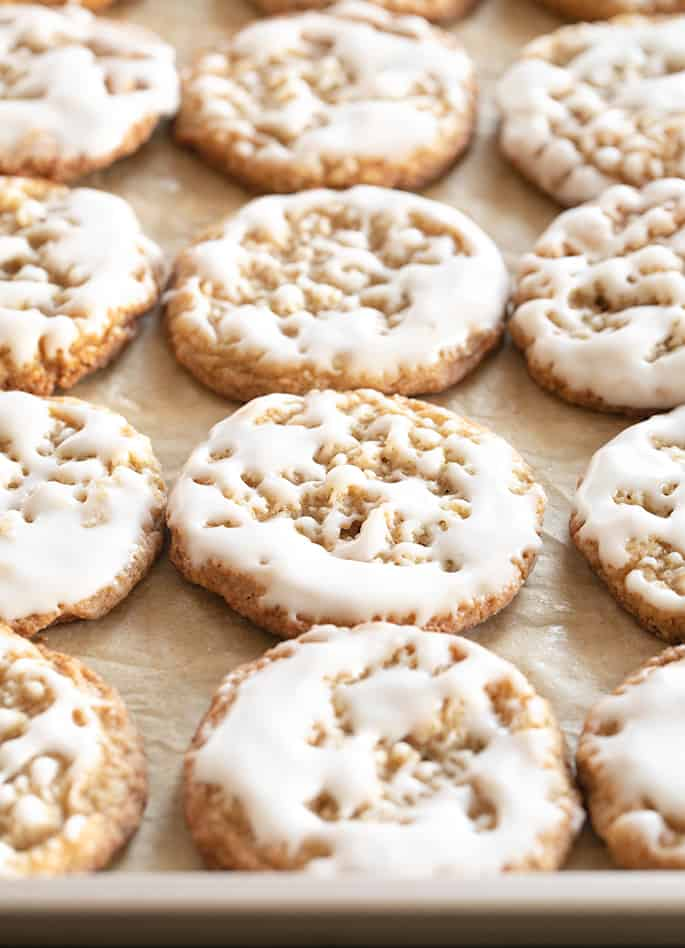 Thin and chewy gluten free oatmeal cookies with light icing on top on a baking tray